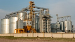 silver silos on agro manufacturing plant for processing drying cleaning and storage of agricultural products, flour, cereals and grain. Large iron barrels of grain. Granary elevator