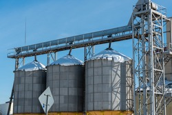 silver silos on agro manufacturing plant for processing drying cleaning and storage of agricultural products, flour, cereals and grain. The granary silo of the elevator is covered with snow in winter