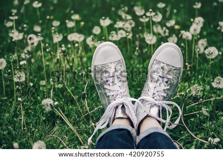 Silver sparkly high top tennis shoes in a field of dandelions #420920755