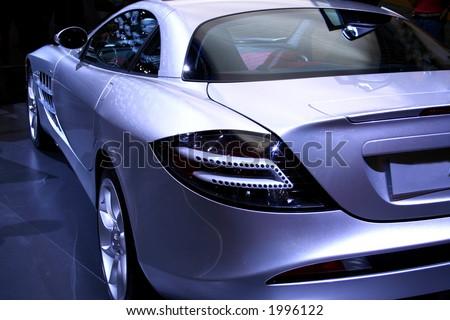 Silver sports car against a dark background. No logo shown.