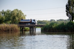 Silver stainless steel tanker truck on concrete bridge over a small river with green reeds. Road bridge with concrete columns.