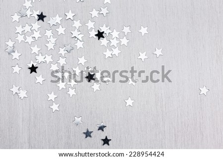 Silver star confetti on brushed metal texture