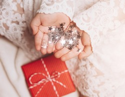 Silver stars sparkling on child's hands and palms. Christmas mood, cozy view. Bright and festive.