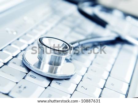 Silver stethoscope on modern silver keyboard