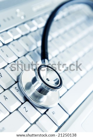 Silver stethoscope on modern silver keyboard