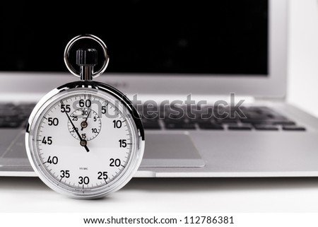 Silver stopwatch with silver laptop in the background