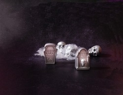 Silver tombstones and sculls covered with spider web on a dark background. Spooky Halloween vibes concept. Banner or party invitation.