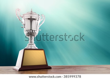 silver trophies on wood table with lighting. copy space ready for your  trophy design.