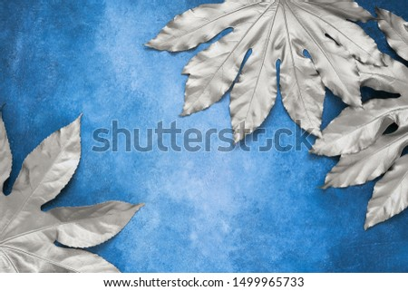Silver tropical leaves on blue backdrop. Minimal summer exotic concept with copy space. Copy space, top view.