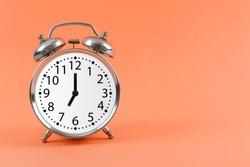 Silver vintage alarm clock on pink background