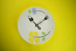 silver wares spoon and fork with cute white ceramic plate on bright yellow background clock like pattern