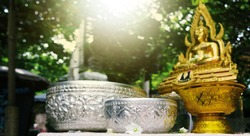 Silver water bowl and golden vintage tray with buddha background on Thailand Songkran festival april