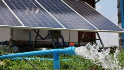 Silver water gushed out of the PVC pipe. The groundwater is pumped by a solar powered pump from a solar panel in a smart agricultural farm. Close focus and choose content
