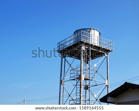 Silver water tank on the tower On a clean blue sky background With copy space stock photo