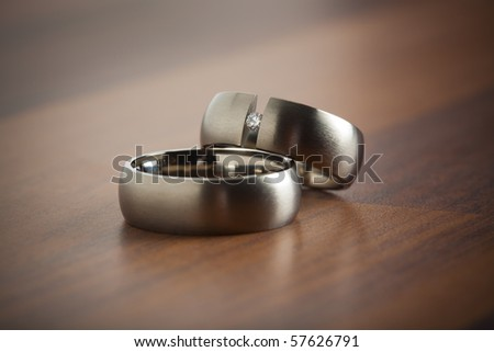 stock photo silver wedding rings laying on table focus on the diamond of