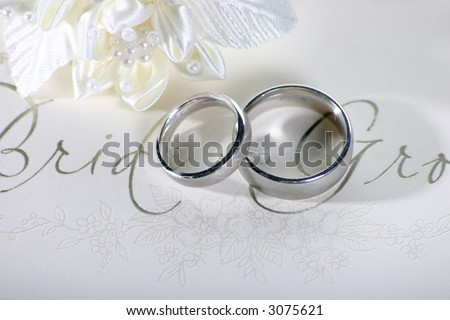 stock photo Silver wedding rings on a card saying Bride and Groom