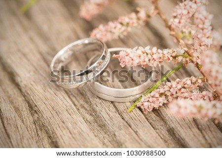 Silver wedding rings on a wooden  background #1030988500