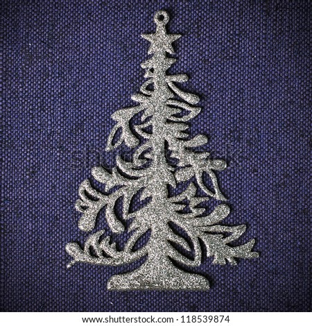 Silver xmas tree on blue canvas background - stock photo