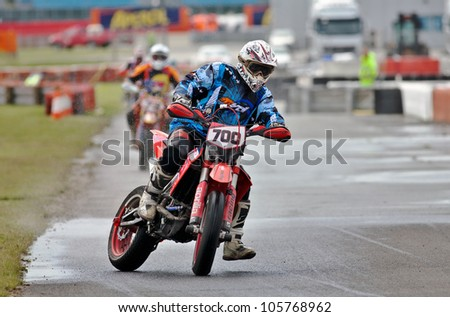 SILVERSTONE, UK - JUNE 15: An unnamed rider participating in the British Supermoto championship slides his bike into a tight left hand corner on a rain soaked track on June 15, 2012 at Silverstone