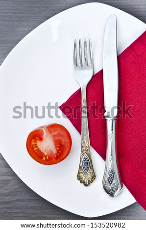 Silverware and a tomato on a plate