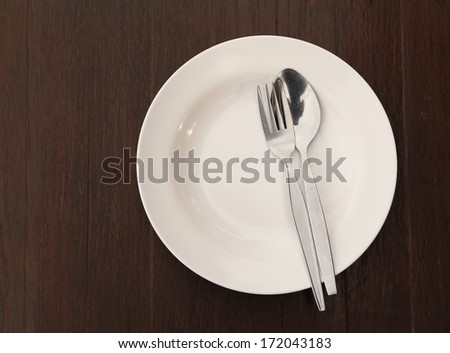 Silverware and plate on wood table