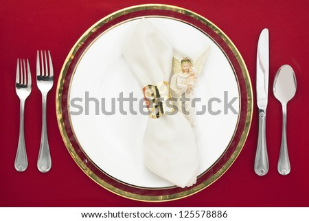 Silverware and plate with white napkin and angel decoration on a red background
