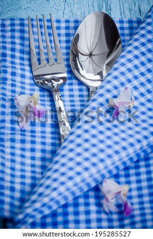 Silverware at napkin on wooden background
