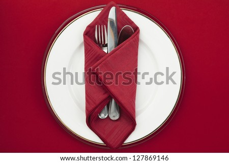 Silverware red napkin on a white plate