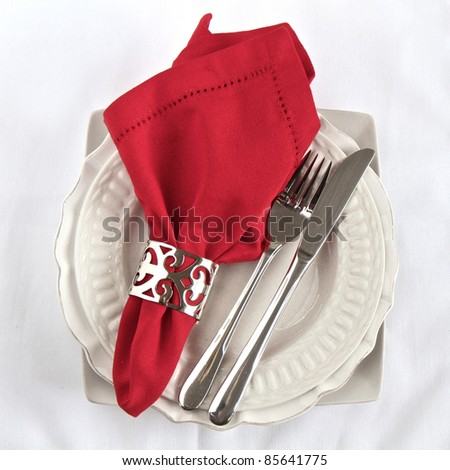Silverware table setting with a red napkin on white linen