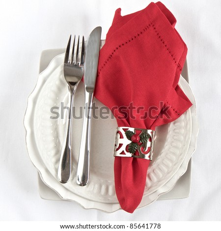 Silverware with red napkin and white plates with a Christmas theme