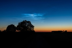 Silvery blue noctilucent clouds (NLC) over the Dutch countryside