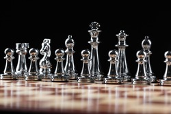 Silvery chess figures standing on wooden chessboard. Intellectual and tactical game. Strategy planning, leadership and teamwork business concept. Close-up steel chess pieces in row on black background
