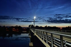 Silvery clouds above the bridge with glowing led lamps. Summer night