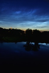 Silvery clouds in the sky after sunset are reflected in the water. Night.