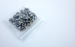 Silvery little bolts in a plastic bag on a white isolate