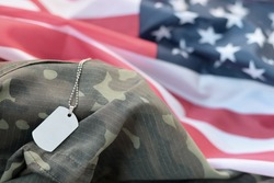 Silvery military beads with dog tag on United States fabric flag and camouflage uniform