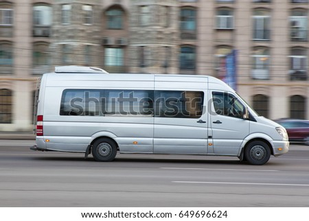 silvery minibus goes down the street the cities #649696624