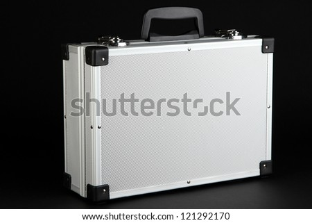 Silvery suitcase on black background