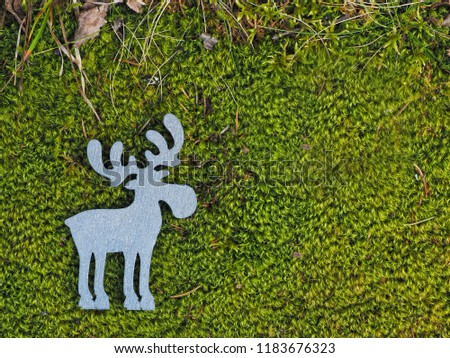 Silvery wooden silhouette of moose, or elk, or deer, lies on lush green forest, swamp moss with dry grass on top edge of picture; with copy space