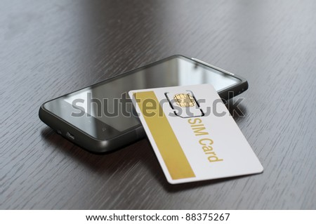 SIM card and mobile phone on table