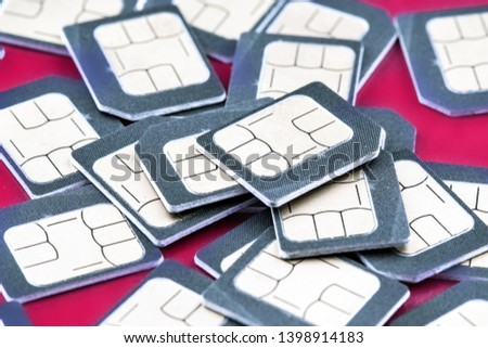 SIM card for phone piled in a pile on a red background