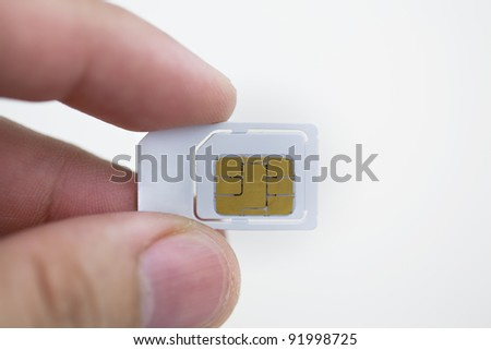 Sim card In a hand isolated on white background. - stock photo