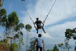 Simarjarunjung, North Sumatera-March 2021: A male plays swing rope at Bukit Indah Simarjarunjung. This game will challenge your adrenalin to the limit.
