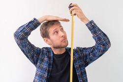 simple adult teenager male person with a roll tape measure the height against the wall