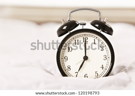 Simple alarm clock on white bed