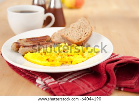 Simple and Delicious Breakfast of Mini Bratwurst Sausages, Eggs Scrambled with Cheese, Toast, and Black Coffee