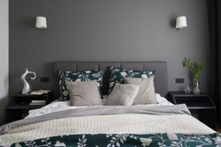 Simple and elegant bedroom with big bed with gray, quilted headboard, two black and modern bedside table with decorations and stylish gray wall