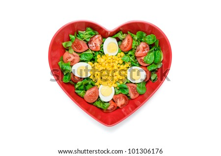 Simple and healthy salad made ?with lettuce, tomatoes, eggs, corn and olive oil.  Served on a plate with a heart shape.