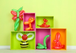 Simple balloon animals and other toys on shelves, on bright background