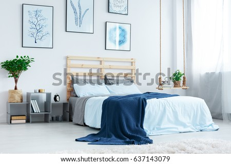Simple bedroom with double bed, blue bedding, posters and window #637143079